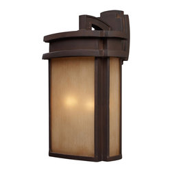 ELK - ELK 42142/2 Outdoor Sconce - Simplicity Of Craft And Form Gives The Sedona Collection A Very Attractive Look Through Its Minimalist Approach.  Inspired By The Architecture And Casual Lifestyle Of The Desert Southwest, This Collection Features Clean Lines With Recessed Edges, Caramel Beige Glass, And A Clay Bronze Finish.