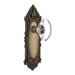 Nostalgic - Nostalgic Passage-Victorian Plate-Oval Clear Crystal Knob-Antique Brass - The Victorian Plate in antique brass, with its distinct curvilinear embellishment, is unmistakably old world vogue. Add our Oval Clear Crystal Knob, with its clean oval shape and smooth outward-curve, and you have the perfect accompaniment for Period, Rustic and Arts & Crafts style homes. All Nostalgic Warehouse knobs are mounted on a solid (not plated) forged brass base for durability and beauty.