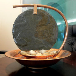 Bluworld - Moonshadow Tabletop Water Fountain - The Large Moonshadow tabletop fountain can bring elegance and tranquility into any room. A Sierra powder coated frame holds a beautiful slate panel suspended over the bowl. The water flows through the top of the frame, down the slate and through a layer of polished river rocks into the waiting pool of water below. These 15 inch water fountains have a quiet, submersible pump that can be adjusted to control the flow rate of the water. There is a halogen accent light to call extra attention to this water feature, even in the dark. Our hand crafted water fountains are small enough to fit on any table and blend into the decor of the room, but still large enough to attract the attention of a discerning eye. Wherever you place the Large Moonshadow fountain, the soothing sound of the falling water is sure to relax and captivate anyone in the room. *Please note that these units are handmade and measurements may vary slightly.