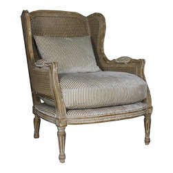 Kathy Kuo Home - Montpelier French Country Buff Wing Back Salon Arm Chair - The carved detailing and open, breezy thatching on this stylish salon chair give it the air of a country European estate. Picture yourself seated in this striped upholstered chair (wearing a white linen suit, of course) overlooking your grounds through a gigantic picture window. The striped, plush cushioned seat means you'll be still be happily sitting there long after night falls.