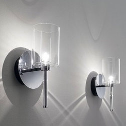 """Axo - Spillray wall sconce AP - Product Details:   The Spillray wall sconcelight by Axowas been designed by Manuel Vivian. This lovely fixture provides stellar halogen lighting. Additionally, the diffuser is available in a variety of colors to choose from. The liquid geometricalforms give this collection of lamps diffused lighting in every direction.    Details:                                  Manufacturer:                            Axo                                                             Designer:                            Manuel Vivia                                                Made in:                            Italy                                                Dimensions:                            Diameter Shade: 5.7"""" (14.5 cm) X Height: 11.5"""" (29.3 cm) X Depth: 3.9"""" (10 cm)                                                Light bulb::                            1 x 20W G4 Halogen                                                Material:                            metal , glass"""