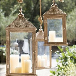 """Elyse Filigree Lantern, Large - Place a pillar candle inside our filigreed lantern to bring out the warmth of the weathered wood and the detail of the handcrafted roof. The lantern's wide design makes it perfect for propping on ledges and mantels - or it can be hung from the loop attached to the decorative finial. Small: 11"""" wide x 6"""" deep x 23"""" high Large: 14"""" wide x 9"""" deep x 31.5"""" high Handmade of die-cut metal. Cypress wood frame with gray hand-washed finish. Glass sides."""