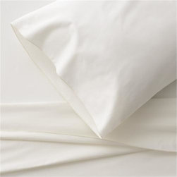 Belo Ivory Extra-Long Twin Sheet Set - Clean, basic white bedding upgrades in soft, smooth cotton percale, beautifully contrasted with a graceful ivory overlocking stitch on the flat sheet and pillowcase. Generous fitted sheet pockets accommodate thicker mattresses. Sheet set includes one flat sheet, one fitted sheet and two pillowcases. Bed pillows also available.