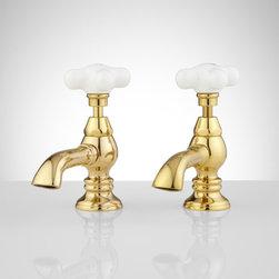 Porcelain Cross-Handle Bathroom Sink Faucets - Elegant porcelain cross handles adorn contoured bases on this basin faucet.