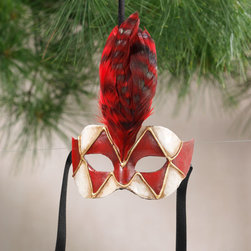 "Exposures - Galletto Mask - Overview Evoke the spirit of the Carnival of Venice with this intriguing miniature galletto mask ornament. The harlequin galletto is one of the most recognizable Venetian mask designs, seeming to reveal a glimpse of Venices secrets behind its mysterious diamond faade. The Venetian artists who make these masks exclusively for Exposures are the very same craftspeople who make the treasured full-size versions. Using century-old Papier-mch and plaster of Paris sculpting techniques, they perfectly capture Venices drama and beauty. This ornament is a perfect gift for mask collectors, travelers and lovers of all things Italian. Features Papier-mch and plaster of Paris  Handcrafted in Italy    Specifications  Measures 5"" wide x 6"" high x 2"" deep"