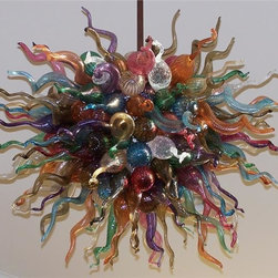 """Belle Meade Hot Glass - Joyous Chandelier - This beautiful chandelier brings joy to everyone who sees it! The artist combines an arsenal of royal jewel tones of individually hand blown glass pods and horns (see additional photos #4 and #5 for details of a""""  pod and horn"""" ) manifesting in this very regal work-of-art. Note- This chandelier is lit from within the armature by easily replaceable 75 watt halogen bayonet bulbs. The lighting system is made from UL listed parts. The armature is shaped appropriate to the chandelier. Note- These chandeliers are suspended by a thin, high strength cable, the length of which must be specified when ordering. The weight for these chandeliers averages 30 pounds per 50 pieces. Due to the many different styles and types available, a ceiling canopy is not provided but can easily be obtained through your electrician. Note- If this item will be viewed from above, such as in a stairwell, the top will need additional pieces covering the armature at additional cost. Please call us for a price quote and specify this when ordering.  LED and Compact Fluorescent lighting are both available. Call for details.  Please note that the price listed pertains to a fixture that will appear very similar to the light shown in the featured photograph and as outlined in the accompanying description.  Virtually all of our artisan crafted fixtures can be customized regarding size, shape, and / or color(s).  Please call for details."""