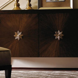 Lexington Furniture - St. Tropez Beauvais Chest - Three drawers and two doors. Four adjustable shelves. Eye-catching radial pattern of quartered walnut on the doors. Jewelry inspired, custom designed star burst pull and knobs. Unique sunburst design. Brass ferrules. Hardware is custom designed in champagne gold finish. Drawer construction: English dovetails, wood runner and guides, drawer stop. Decorative metal in burnished gold. Warranty: One year limited. Made from quartered and cathedral walnut veneers on select hardwood solids. Rich walnut brown finish with medium luster. 56.25 in. W x 15.25 in. D x 39 in. H (235 lbs.). Special Care Instructions from Lexington FurnitureSt. Tropez is an elegant interpretation of transitional design. While the collection has a couture appeal, the designs reflect an unpretentious feeling of luxury and comfort. The resort of St. Tropez is an international destination, with a marvelous blend of cultures, fashion and style. The roots are solidly traditional, but the vibe is chic and casual. The common thread, from a design point-of-view, is elegance without pretense. That is the essence of this collection glamour redefined. Where the beauty of traditional meets the sparkle of contemporary. St Tropez is an elegant interpretation of timeless transitional design. Shimmering silks and soft velvets take their cue from couture fashion. Every texture, every detail is purposely designed to distinctly surround and affirm the home in beauty and glamour.