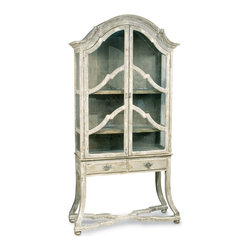 Dutch Cabinet with Glass Doors and Drawers - Cherished treasures are all the more precious when displayed in this glass-fronted cabinet. A beautiful choice for a china hutch or curio cabinet, this glass-fronted vitrine armoire stands on slender flared legs and features an arched top with rich crown molding, double framed doors closing over three deep shelves, and a pair of drawers beneath to tuck small linens or other necessities. All of the woodwork has been given a labor-intensive artisan rubbed whitewash finish, with elegant hardware to match.