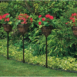 Woodstream - Bronze Coco Liner/Mild Steel Queen Elizabeth Parasol Stake Planter - SPQE-BZ - Shop for Planters and Pottery from Hayneedle.com! The Queen Elizabeth Parasol Stake Planter is constructed from powder-coated steel and has a rich bronze finish that will complement any outdoor decor. The flared vertical wire planter is attached to a 5-inch stabilized stake and has three 14-inch stake sections that offer various height adjustments. The Queen Elizabeth Parasol Stake Planter can be used in multiples to line sidewalks and driveways; they can be scattered throughout gardens set alongside patios decks gazebos or used to accent entrances. These stake planters are completely portable and can be paired with Queen Elizabeth hanging baskets to complete the multi-level theme. Each planter comes with a natural coco liner that promotes plant growth by retaining moisture and evenly distributing nutrients in the soil. About Woodstream and CobraCo A privately held company with a long-standing positive reputation Woodstream is a global manufacturer and marketer of quality products from pets and wildlife control and home and garden products to bird feeders and garden decor. They have a 150-year history of excellence growth and innovation and have built a strong presence in key markets through organic growth and strategic acquisitions. Most recently Woodstream acquired CobraCo which offers an extensive line of planters baskets flower boxes and accessories. The growth of Woodstream is thanks to their customer-driven approach to product development a dedicated design organization that focuses on innovation quality and safety as well as a commitment to an industry-leading level of service.