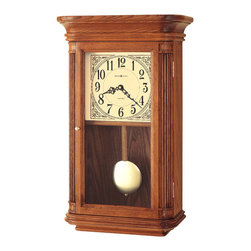 "Howard Miller - Howard Miller - Pennington Wall Clock - Here is a beautiful wood wall clock with a polished brass finished bob on a wooden pendulum. The dial features a lamb's wool finish with black ornate numerals and fancy scroll work in the corners. This is also a chime clock and plays Westminster or Ave Maria, and has a volume adjustment and an automatic nighttime chime shut-off option. * This wall clock features soft, rounded corners on the fully molded base, with a flared, molded bonnet. . Reeded corner columns and a polished brass pull enhance the door. . The lamb's wool dial features black Arabic numerals, decorative corner accents, black serpentine hands, and a glass crystal. . A polished brass finished bob on a wooden pendulum adds the finishing touch. . Finished in Oak Yorkshire on select hardwoods and veneers. . Quartz, dual chime movement plays Westminster or Ave Maria chimes, and features volume control and automatic nighttime chime shut-off option. . H. 21-1/2"" (54 cm). W. 13"" (33 cm). D. 6-1/2"" (16 cm)"