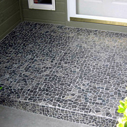 """Tumbled Black Marble Tile at the Entry Of A House - This tumbled black marble tile at the entrance of this home creates a lot of interest.  The tiles are 'interlocking,' so there is no 'square tile' grout lines.  The """"Delorean Gray"""" grout outlines each piece of stone, giving the impression each little piece of stone was individually set in place.  Also available in tumbled mixed onyx, tumbled red marble & tumbled white marble."""