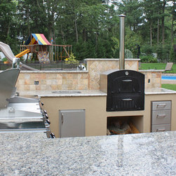 Outdoor Kitchen - Fire Magic outdoor kitchen featuring Fire Magic Echelon Grill with access doors, drawers, and Tuscan Chef wood burning pizza oven. Stucco finish on base with granite countertop & tile back splash.