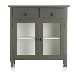 Stretto Entryway Cabinet - Handcrafted entryway cabinet charms with the clean, casual look of Scandinavian Gustavian furniture. Custom colors coat its neat lines in warm grey opening to an off-white interior behind two glass doors. Narrow, slim profile with interior shelf and two drawers provides just the right amount of space to greet keys, purses, mail and more in entryway or small room. Antique hardware, including ring pulls and faux key handle, adds to its time-honored style. Cabinet may exhibit graining, knots, splitting and mineral deposits, naturally occurring and prized attributes of pure wood.