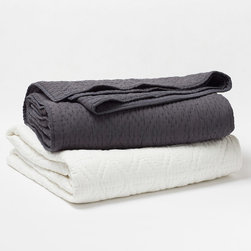 """Coyuchi - Coyuchi Swiss Dot Quilt - The Coyuchi Swiss Dot quilt's plush design exudes a contemporary, soothing vibe. On smooth, cotton voile, delicate round stitches form sophisticated diamond patterns. Available in full/queen and king sizes; Available in charcoal gray or white; 100% organic cotton; Due to handmade quality, slight variations in fabric may occur; Machine washable; Full/queen: 86""""W x 86""""H; King: 100""""W x 86""""H"""