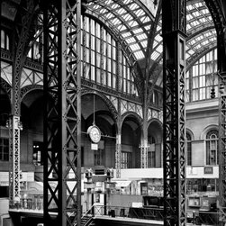 Pennsylvania Station, 370 Seventh Avenue, Concourse from Southwest Print - Pennsylvania Station, 370 Seventh Avenue, West Thirty-first, Thirty-first-Thirty-third Streets, New York, New York, NY. Cervin Robinson, Photographer April 24, 1962. Other Title: Penn Station Related Names: Charles Follen McKim, William Rutherford Mead, Stanford White. Photo 5 x 7 in. Building/structure dates: 1903 initial construction Building/structure dates: 1963 demolished Significance: The construction of Pennsylvania Station was one part of a large building program undertaken in 1903 by the Pennsylvania Railroad Company. Included in this program was the construction of tunnels under the North River, which enabled Pennsylvania Railroad trains to enter Manhattan directly from New Jersey for the first time. Because the trains entered on tracks below ground level, the architects did not follow any of the more common architectural forms for a railway station and designed instead a rather low, colonnade facade...The rich sequences of spaces in the terminal culminated in the great concourse with its glass and steel roof. The design of the main waiting room was reputedly based on the Roman Baths of Caraculla. From a planning standpoint, the station was important for its separation of various forms of transportation on different levels and for the convenience of its many entrances and exits to the city. Pennsylvania Station was built during the Golden Age of railroading, when its owners intended the terminal not only to serve the specific needs of the railroad by also to embellish the city as a monumental gateway.