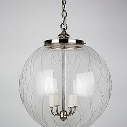Sorenson 18 Lantern - Although it's a bit difficult to tell from a distance, the glass of this lantern is netted — referencing a time when factory lighting was netted for safety. The thick mouth blown glass is wrapped in a handwoven wire fabric, creating unique swirls and striations in the glass itself.