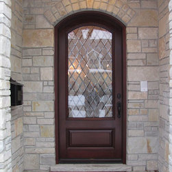 Stone Arched Doorway with Mahogany Wood Front Door - An arched mahogany wood door in a stone doorway Installed by Opal Enterprises in Lisle, IL