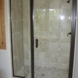 "Shower Doors with In Line Panel - Continuous hinged door hanging off of right with 6"" through-the-glass pull handle. It has two 45 degree panels to left of door where we have glazed them eliminating the channel. Hardware is oil rubbed bronze with ¼"" clear tempered glass."