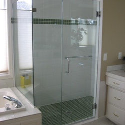 """Framless Return Shower Doors with Knee Walls - Shower enclosure is fabricated with ½"""" clear tempered glass with polished chrome hardware. The door has an alternate handle option which has a pull handle on one side and a towel bar on the other. This handle option could also have been installed with the bar on the outside of the door and the pull handle on the inside."""