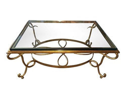 Used Baker Vintage Iron and Glass Coffee Table - This vintage Baker coffee table has a heavy, gilded iron base, while the top is a substantial piece of beveled glass - at least one inch thick. This piece most likely dates back to the 1970s, but it's contemporary styling and excellent condition makes it still very versatile.
