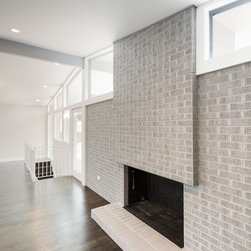 Dexter Mid-mod - Wood burning fireplace.  Typically we like to leave brick alone, but the original brick was so dark that this corner of the room felt uninviting. With lighter paint colors, the entire space feels more light an airy. Photo by Michael de Leon Photography.