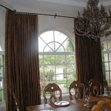 Custom Draperies - Hand drawn silk draperies with top tacked pleats, accent banding and tassel trim on side hems, Installed on small iron poles with matching iron rings.