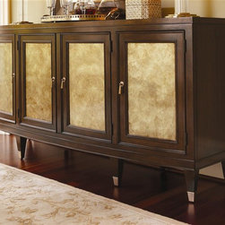 Lexington Furniture - St. Tropez Riviera Buffet - Custom designed tassel hardware. Four doors with gold burnished silver leaf panels. Five adjustable shelves. Brass ferrules. One felt lined drawer and is divided for silver. Drawer construction: English dovetails, wood runner and guides, drawer stop. Made from quartered and cathedral walnut veneers on select hardwood solids and gold burnished silver leaf accents. Rich walnut brown finish with medium luster. 78.25 in. W x 20.25 in. D x 38 in. H (305 lbs.). Special Care Instructions from Lexington FurnitureSt. Tropez is an elegant interpretation of transitional design. While the collection has a couture appeal, the designs reflect an unpretentious feeling of luxury and comfort. The resort of St. Tropez is an international destination, with a marvelous blend of cultures, fashion and style. The roots are solidly traditional, but the vibe is chic and casual. The common thread, from a design point-of-view, is elegance without pretense. That is the essence of this collection glamour redefined. Where the beauty of traditional meets the sparkle of contemporary. St Tropez is an elegant interpretation of timeless transitional design. Shimmering silks and soft velvets take their cue from couture fashion. Every texture, every detail is purposely designed to distinctly surround and affirm the home in beauty and glamour.