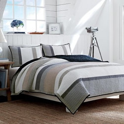 Nautica Hayward Cotton Reversible Quilt with Optional Shams - Keep things cool and classic in the bedroom with the simple style of the Nautica Hayward Cotton Reversible Quilt with Optional Shams. Crafted from 100% yarn-dyed cotton, in beautiful, neutral shades of gray, white, beige, and navy, this quilt is destined to be a favorite for years to come. Available in your choice of size to best suit your needs, you also have the option to complete the look by adding on the optional shams.Quilt Dimensions:Twin: 68 x 88 in.Full/Queen: 90 x 90 in.King: 104 x 96 in.About NauticaNautica offers quality, design, and value while capturing the essence of an active, adventurous, and spirited lifestyle. Nautica took its name from the Latin word Nauticus for ship. Since one of mankind's first accomplishments in exploring the world was to take to the seas, a spinnaker logo was designed as a symbol of adventure, action, and classicism.Founded in 1983, Nautica has evolved from a collection of men's outerwear to a leading global lifestyle brand with products ranging from men's, women's, and children's apparel and accessories to a complete home collection. Now part of VF Corporation, a leader in branded quality apparel, Nautica has become one of the most important American lifestyle brands throughout the world.