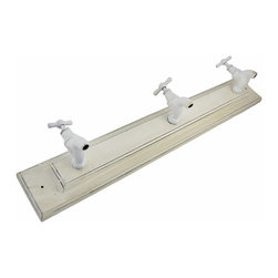 Antique White Spigot Wall Mounted Rack - This wall mounted rack is a wonderful addition to your bathroom, laundry room, or garage. It features 3 white metal spigots, spaced 7 inches apart, that are perfect for hanging up towels or clothing. The piece measures 24 inches long, 4 1/2 inches tall, 4 1/2 inches deep and has an antiqued finish. Pre-drilled holes on either side make it easy to mount to the wall, and hardware is included.