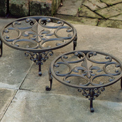 Fleur De Lis Plant Stands (Set of Two) - These plant stands are great looking and you can never have enough of them. Stands like this keep your pots up off the ground, giving them room to drain properly outdoors, and keeping them from ruining your favorite floors indoors. It's actually quite a shame that the fleur de lis will be covered during the warm season.