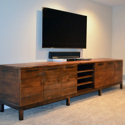 """Reclaimed wood media center console - This contemporary media console was custom made to help fill a very large basement space. The client was unable to find anything in stores close to the size she wanted. It was a challenge constructing and transporting the 10' x 30""""x20"""" finished piece. The top, sides and doors were made using reclaimed barn wood and stained dark to match the décor.  New walnut was chosen for the base and interior cabinet space. Matching rustic floating shelves are going to be added to either side of the TV to complete the design."""