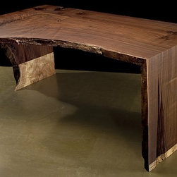 Desk No. 0081 by John Houshmand - This deconstructed black walnut desk is a juxtaposition of unfinished edges and hand carved design. The two toned feature of the legs' base creates a distinct accent that gives an impression of the table being raised off the ground. The carved out inner crux of the desk is lightly sanded down leaving an indelible image of a roughly hewed rim. A most unique desk.
