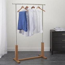 Garment Rack - Our exclusive rack designed by Mark Daniel is a stylish, functional option for extra garment storage, guest coats and closet-space extension. Handsome wood trestle base supports the steel frame and hanging bar that extends to four feet. Rack has a 100-pound capacity and adjustable levelers for stability.