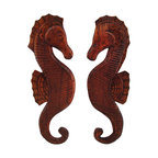 Pair of Hand Carved Mahogany Seahorse Wall Hangings - This pair of hand-crafted mahogany seahorses beautifully complements beach and nautical decor. They are mirror images of one another, and each measures 19 inches tall, 6 inches wide and 1/2 inch thick. Each one hangs on the wall with a single nail or picture hanger. This set makes a great gift, and is a wonderful addition to porches or patios.