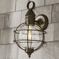 """Fisherman's Sconce - Modeled after the caged designs of traditional fisherman's lanterns, our sconce lights the way in nautical style. The steel frame is distressed by hand for a rustic, weathered look that creates a handsome contrast to the spherical blown-glass shade. 9"""" wide x 9"""" deep x 15.5"""" high Crafted from steel with a hand blown glass shade; finish is hand-applied in aged iron. Damp UL-listed for use indoors or in a protected outdoor area. Hardwire; professional installation recommended."""