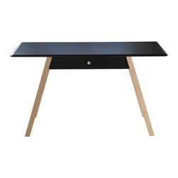 Steuart Padwick - Pitch Bullet Desk | Steuart Padwick - Design by Steuart Padwick, 2012.The Pitch Bullet Desk is an understated design with simple and clean detailing, ideal for a range of household aesthetics from transitional to modern. The design features a painted black top and drawer front contrasted by angled oak legs and a center drawer pull in a clear lacquer finish. Its stark color contrast is softened by the tabletop's beveled edge detailing, which offers a smooth and refined finish to an otherwise sharply angled form. A spacious central drawer on traditional wooden runners provides storage space for concealing gadgets, tools, and documents and keeps its surface free of clutter.