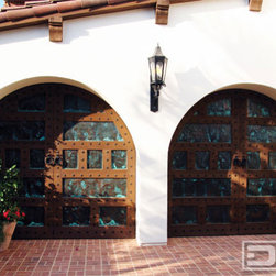 Dynamic Garage Door - California Dream 08 | Custom Made Spanish Style Garage Doors in Santa Barbara CA - Santa Barbara, CA is home to some of the most astonishing Spanish Colonial style homes. These custom Spanish Garage Doors were handcrafted out of brushed, clear cedar wood, these custom arched tops were designed to follow the home's Spanish arched opening that lead to the garages.  They are beautifully adorned with hammered copper plate inserts that give these Spanish garage doors that turquoise green color that make them pop. The rustic iron clavos line every wooden trim piece on these Spanish garage doors bringing out that unmistakable Spanish Colonial Style.  These Santa Barbara Spanish Garage Doors are the perfect match to your Santa Barbara Style home.