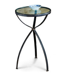 Glass Top Table in Bronze - It would be well placed within an elegant-industrial loft, an eclectic carriage house, a summer bungalow by the shore; such is the versatility of the Glass Top Table in Bronze. The simple construction of the three iron legs imparts an airy aesthetic to the piece, as does the iron-rimmed glass top.