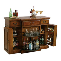 Howard Miller - Howard Miller Shiraz Bar - 695084 - Shop for Bars and Bar Sets from Hayneedle.com! The Shiraz Hide-A-Bar console features an elegant Indian Summer finish on select hardwoods and veneers. This raised door panel cabinet offers generous room for wine and spirits. Each side features an adjustable shelf and storage on the inside of each door. In the center of the console is a Lazy Susan-style pivoting door with two fixed shelves providing additional room for bottle and glass storage. The top surface has a planked style look with a hand planed surface and various forms of distressing. Three upper drawers hold serving utensils bar cloths and other items.Additional features of this bar include:Hanging stemware rackPad-Lock metal shelf clipsLocking doors on both side cabinets and the center pivoting cabinet keep wines and spirits secureAdjustable levelers under all cornersThe Howard Miller StoryIncomparable workmanship unsurpassed quality and a quest for perfection - these were the cornerstones of the company Howard C. Miller founded back in 1926 at the age of 21. Even then Howard Miller understood the need to make products that would be steeped in quality and value.In 1989 Howard Miller began creating collectors' cabinets with the same attention to detail and craftsmanship inherent in their clock-making. Fashioned from glass and hardwoods Howard Miller cabinets are ideal for displaying heirlooms plates glassware and other collectibles.A highly respected brand Howard Miller maintains its popularity because of the company's commitment to quality. Every product manufactured at the company's sprawling facility in Zeeland Michigan undergoes stringent tests and exceeds industry standards to ensure a lifetime of enjoyment.