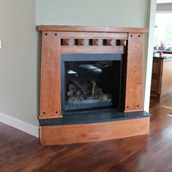 """Mantles - A taste of rustic in this mantle made of select alder.  This piece features an arched hearth and top, pyramid end corbels, and 1"""" pyramid clavos.  We designed this mantle to fit within the constraints of the small wall it is attached and compliment the mission style cabinetry in the kitchen beyond."""