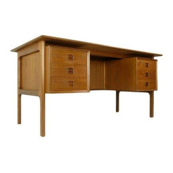 Pre-owned Omann Junior Mid-Century Modern Danish Teak Desk - A stunning Mid-Century teak desk made in Denmark by Omann Junior. This free standing desk does it all. It features a bookcase at the back and 6 drawers at the front. The top drawers on the left and on the right can be locked. Key included.    The desk is in fantastic condition overall. Rich warm teak color. The floating top has been cleaned and oiled. There is a darker area on the desk surface where it had been covered by a writing mat for a long time. Please note the scratch on two of the drawers and 2 screw holes on the left side that have been filled. These are minor signs of wear and do not distract from the overall beauty of this stunning piece.