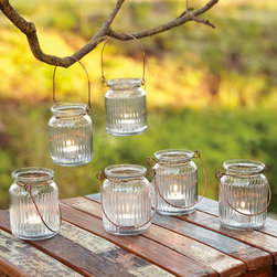 Jelly Jar Tea Light Lanterns - These charming glass lanterns hold tea lights and would look so sweet at a wedding. I'd like a couple jelly jar lanterns in my bathroom, since they're just the perfect size.