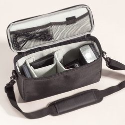 """JILL-E Designs - Camera Insert - Overview The perfect solution for the on-the-go photographer, the Camera Bag Insert means no longer is it necessary to carry both a camera bag and another bag. Perfect for sightseeing, events, or even everyday use, this sturdy black nylon camera bag insert has a variety of uses. The zippered top opens to reveal a flexible storage space. The roomy interior with velcro dividers fits your camera and plenty of extra gear with customizable compartments. Mesh pockets in the inner top and a zippered pocket on the back of the bag make it easy to store additional gear, your phone, or keys. A padded removable shoulder strap makes this bag transportable on its own. Perfect for anyone from a busy mom, who needs one less bag to carry, to a traveler looking to save space - or, even a professional photographer!  Features Black nylon camera bag Zippered opening Includes detachable shoulder strap  Specifications Measures 6""""H x 10 1/2"""" wide x 3"""" deep"""