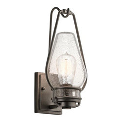 Kichler - Hanford Outdoor Wall Sconce by Kichler - A warm, welcoming accent for exteriors. The Kichler Hanford Outdoor Wall Sconce offers charming antique ambiance with its lantern-like design. A sturdy Anvil Iron frame holds the Clear Seedy glass shade for a rustic look. The decorative lantern hook atop the wall plate adds authentic appeal and stability. Since 1938, Cleveland-based Kichler Lighting has created exceptional lighting in a variety of styles, finishes, colors and designs. With a diverse collection of indoor and outdoor lighting in classic and contemporary styles, Kichler Lighting always focuses on making home lighting that is both beautiful and functional.