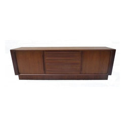 Pre-owned Danish Teak Tambour Door Credenza - High style and tons of storage. We love this Mid-Century Modern credenza for it's beautiful grained teak, finished back, and endless storage space. One drawer has a light stain in the grain (although it's not visible when the doors are shut) and there's a few small veneer chips to the base, and light scratches to the top. Overall a long and low Danish credenza for your mod pod!