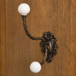 Large Ornate Brass Double Hook with Porcelain Knobs - Antique Brass - This knob features a detailed mounting plate and delicately twisted hooks. Finished with matching porcelain knobs, you can add function and beauty to any room.