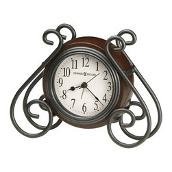 Howard Miller - Diane Tabletop Clock w Decorative Metal Frame - Lavish scroll arms visually support this round, table top clock. Metal alarm clock has a soothing and medium-toned brown finish that will blend nicely with any d̩cor. The dial is illuminated with a soft light that glows in the dark. Includes an AC adapter. Decorative metal wire alarm clock with medium-brown finished case. The dial is illuminated with a soft back light that creates a continuous ���glow� in the darkness. The dial light is powered by an AC adapter, which is included. The off-white dial offers black Arabic numerals and black hands, with silver second and alarm hands. Glass crystal protects the dial. Quartz movement with snooze and crescendo alarm includes the battery. 6 1/2 in. W x 2 in. D x 5 1/4 in. H