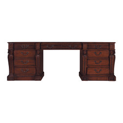 Pedestal Desk - Baker Furniture - This fine William Kent carved mahogany partners Pedestal Desk has a rectangular top with a molded border and inset with a tooled leather panel. The desk is fitted with one long and two short drawers in each frieze, one short drawer and one file drawer in each pedestal, all with shaped gilt brass swan necked drop handles. Each pedestal is flanked by carved termes surmounted with finely carved lion's masks clasping brass rings. The lower section is carved with acanthus leaves and fish scales and terminates to scrolls on a square shaped plinth carved with gadroon ornament. The desk comes standard in Faded Mahogany finish. English c. 1740.