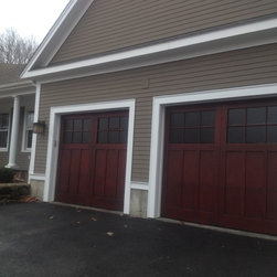 Carriage House Doors - Two custom African Mahogany doors with marine grade mahogany plywood panels and mahogany colored stain and square lites.
