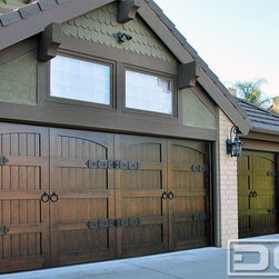 Custom Wood Garage Doors With Decorative Dummy Hardware Made in Orange County CA - These custom wood garage doors were custom designed and crafted by Dynamic Garage Door of Orange County, CA. These custom overhead garage doors feature hand forged decorative hardware which gives them the look of swing out carriage door but in reality they roll up into the overhead like a conventional sectional garage door with automatic openers. The iron ring pulls beautifully bejewel the overall essence of swing open carriage doors. The wood used on these doors is select tight knot cedar stained dark to flow with the home's Tudor style.